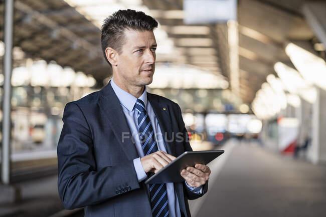 Бізнесмен користується планшетом на залізничній станції. — стокове фото