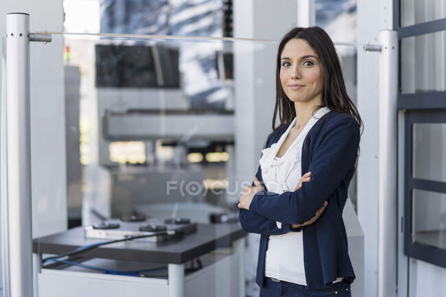 Portrait of smiling businesswoman in a modern factory — Stock Photo