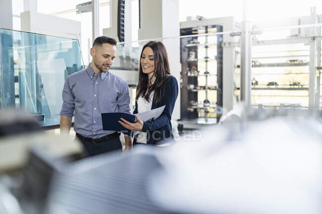 Smiling businessman and businesswoman looking at folder in modern factory — Stock Photo