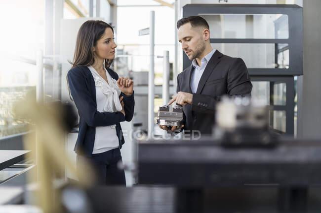 Empresario y empresaria examinando pieza de trabajo en fábrica - foto de stock