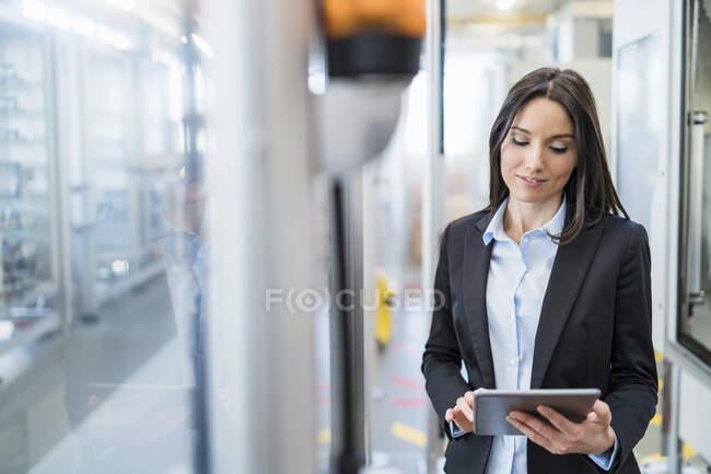 Безробітна жінка на сучасній фабриці користується планшетом. — стокове фото