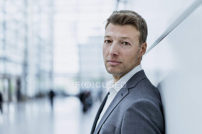 Portrait of businessman leaning against a wall — Stock Photo