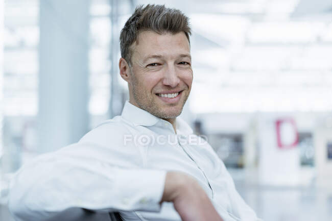 Портрет усміхненого бізнесмена, який сидить у залі очікування. — стокове фото