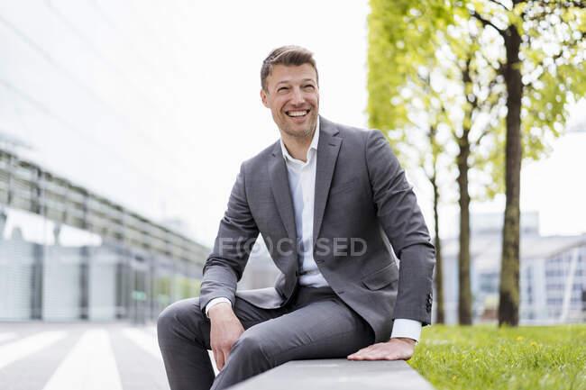 Empresário feliz sentado lá fora na cidade — Fotografia de Stock