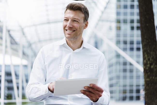 Hombre de negocios sonriente con tableta afuera en la ciudad - foto de stock
