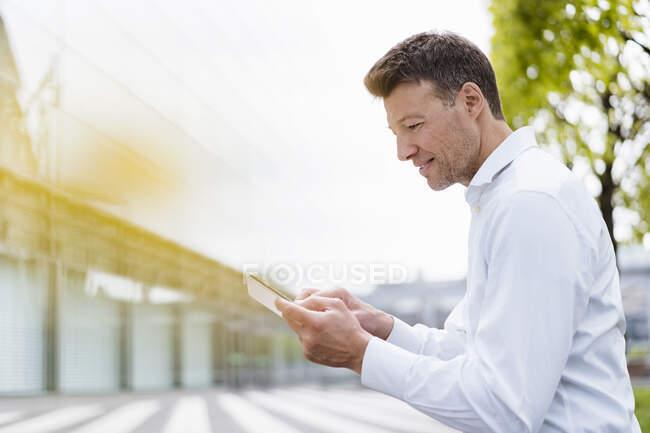 Empresario usando tableta afuera en la ciudad - foto de stock