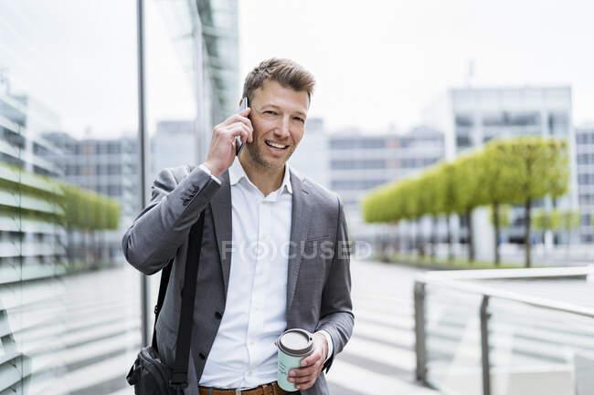 Empresario en celular en movimiento en la ciudad - foto de stock
