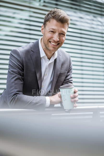 Retrato de un hombre de negocios sonriente con café para llevar afuera en la ciudad - foto de stock