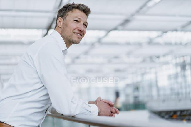 Hombre de negocios sonriente apoyado en la barandilla - foto de stock