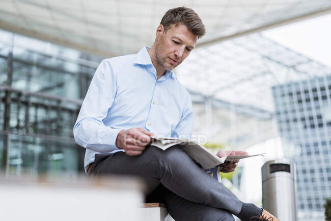 Empresario sentado afuera en el periódico de lectura de la ciudad - foto de stock