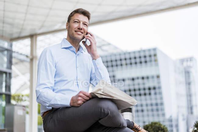 Empresario fuera en la ciudad en el teléfono celular - foto de stock