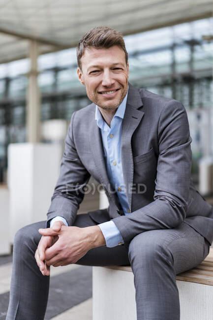 Retrato de un hombre de negocios sonriente sentado afuera en la ciudad - foto de stock