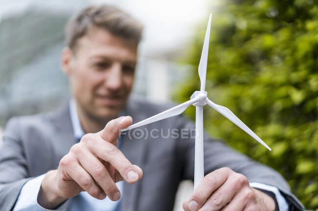 Businessman with wind turbine model outdoors — Stock Photo