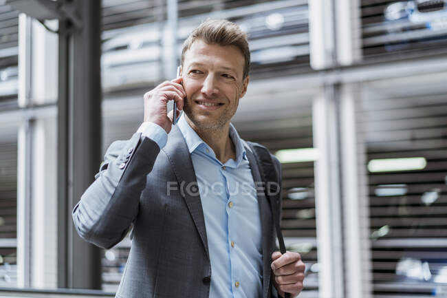 Portrait of businessman on cell phone at car park — Stock Photo