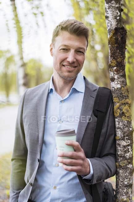 Smiling businessman with takeaway coffee in a park — Stock Photo