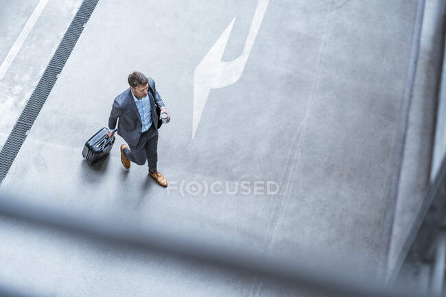 Top view of businessman walking with baggage and takeaway coffee — Stock Photo
