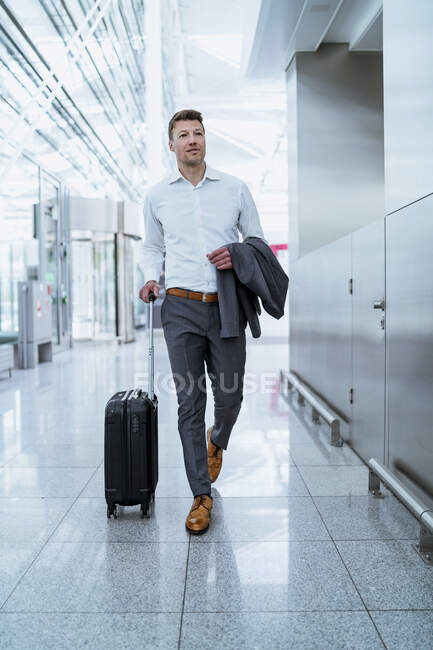 Businessman walking with baggage at the airport — Stock Photo