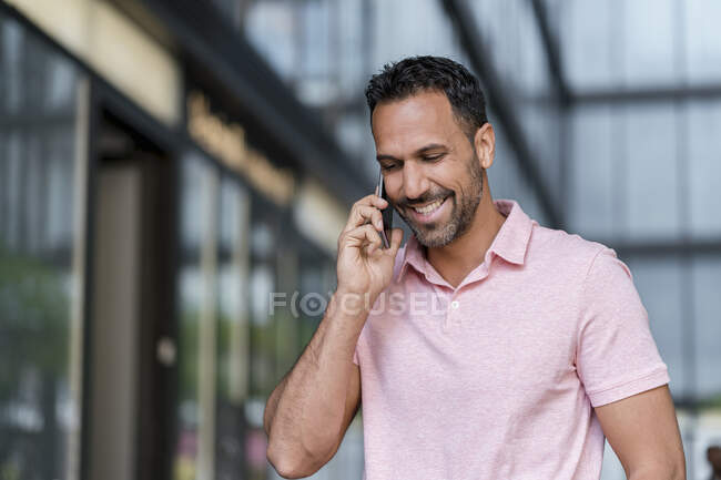 Smiling man on cell phone in the city — Stock Photo