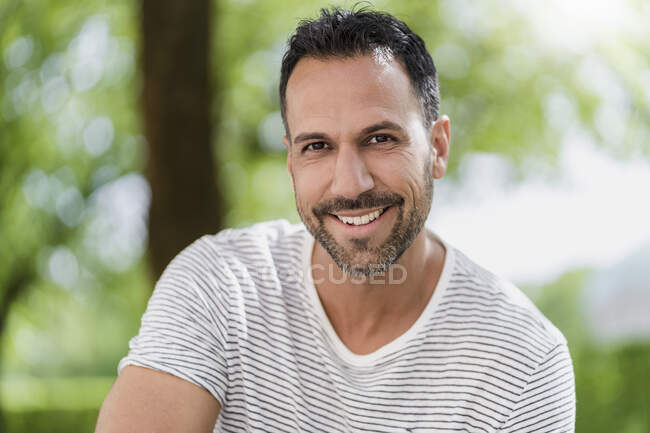 Portrait of smiling man in a park — Stock Photo