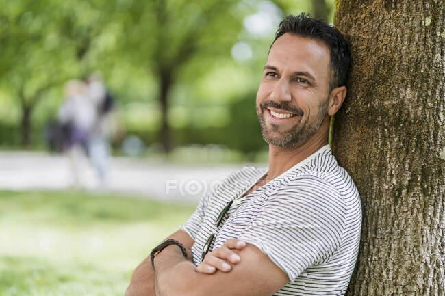 Porträt eines lächelnden Mannes, der sich im Park gegen einen Baum lehnt — Stockfoto