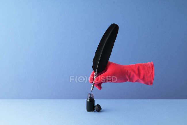 Pluma de pluma sostenida en la mano y sumergida en tintero sobre fondo azul - foto de stock