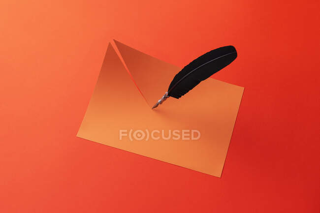 Pluma Quill cortar el papel por la mitad sobre fondo rojo - foto de stock