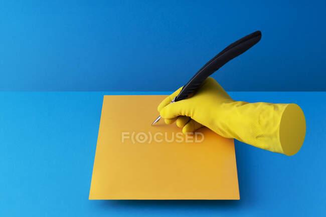 Pluma de pluma sostenida en la mano y escritura sobre papel naranja sobre fondo azul - foto de stock