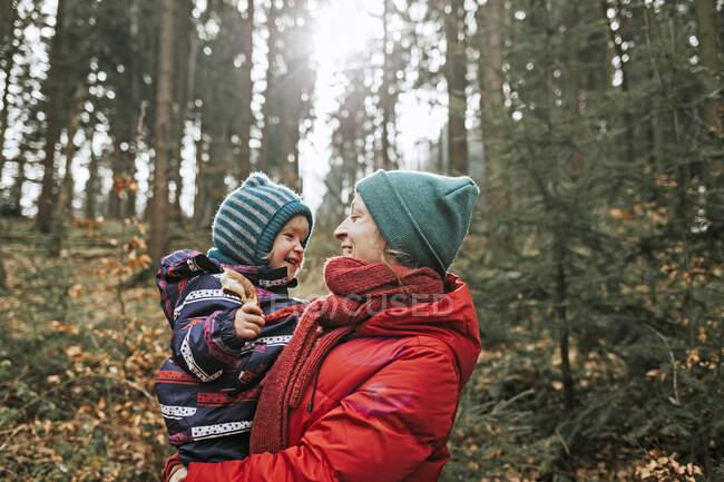 Мама носила щасливу маленьку донечку в лісі. — стокове фото