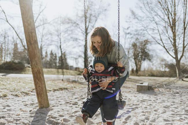 Мама зі своєю донечкою гойдається на ігровому майданчику. — стокове фото