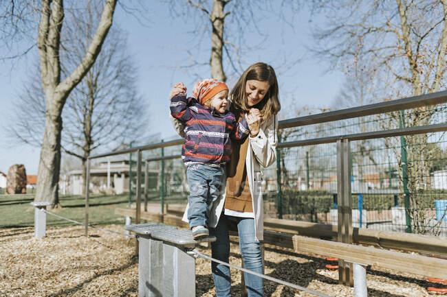 Щаслива мати з маленькою донькою на ігровому майданчику. — стокове фото