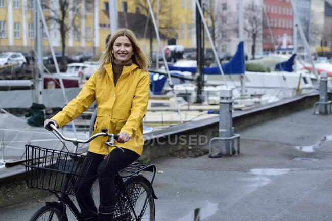 Dinamarca, Copenhague, mujer feliz montar en bicicleta en el puerto de la ciudad en tiempo lluvioso - foto de stock