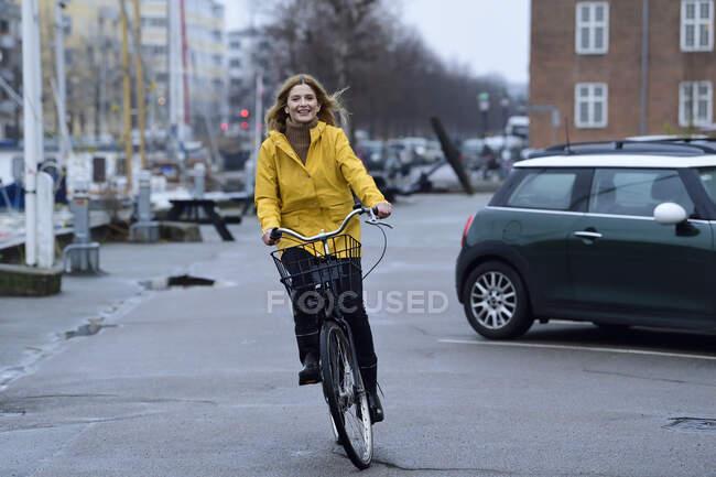 Dinamarca, Copenhague, mujer feliz montar en bicicleta en el paseo marítimo en tiempo lluvioso - foto de stock
