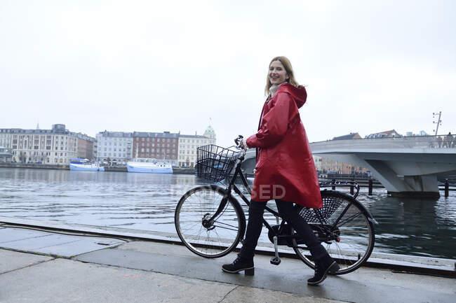 Dinamarca, Copenhague, mujer feliz empujando bicicleta en el puerto de la ciudad en tiempo lluvioso - foto de stock
