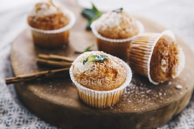 Muffin fatti in casa con cannella e menta su tavola di legno — Foto stock