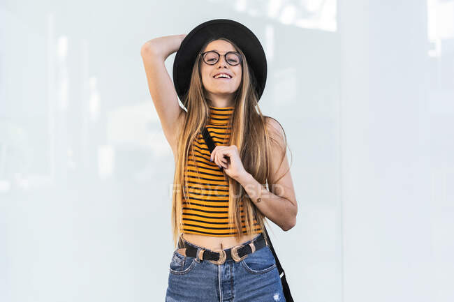 Portrait of happy teenage girl wearing hat and glasses — Stock Photo