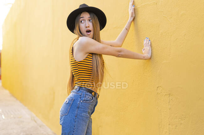 Portrait of surprised teenage girl wearing hat at yellow wall — Stock Photo