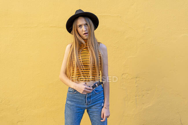 Portrait of annoyed teenage girl wearing hat at yellow wall — Stock Photo
