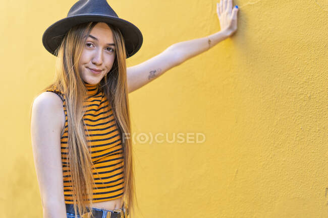 Portrait of teenage girl wearing hat at yellow wall — Stock Photo
