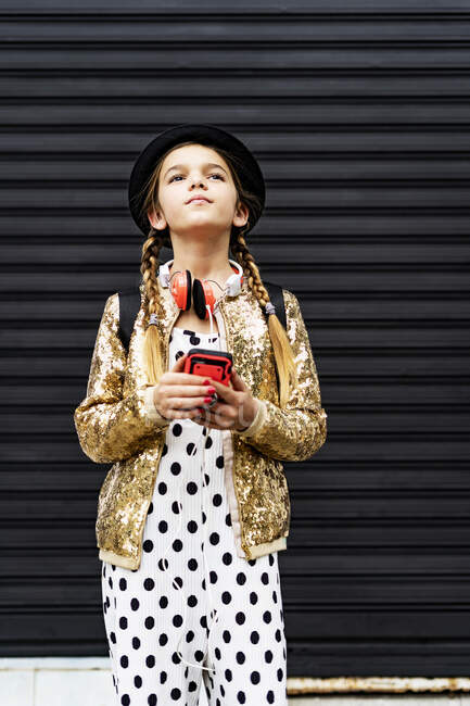 Portrait of girl with smartphone wearing hat, golden sequin jacket and polka dot jumpsuit thinking — Stock Photo