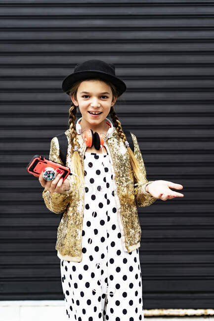 Portrait of smiling girl with smartphone wearing hat, golden sequin jacket and polka dot jumpsuit — Stock Photo