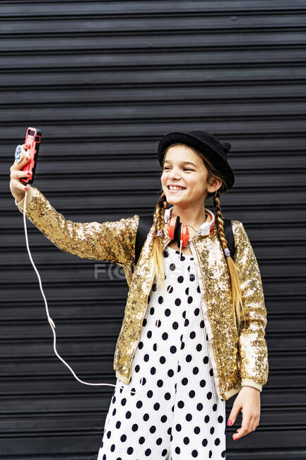 Portrait of smiling girl wearing hat and golden sequin jacket taking selfie with smartphone — Stock Photo