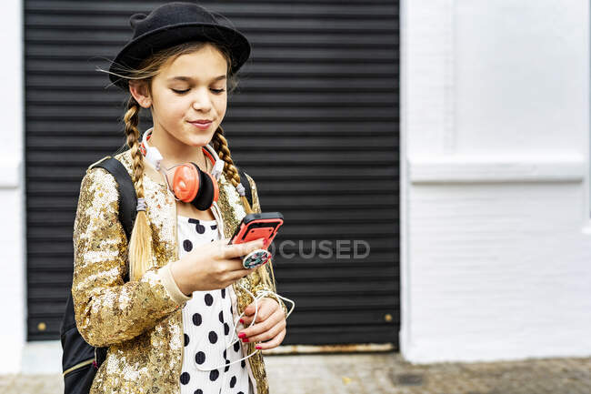 Portrait of girl with headphones wearing hat and golden sequin jacket looking at cell phone — Stock Photo