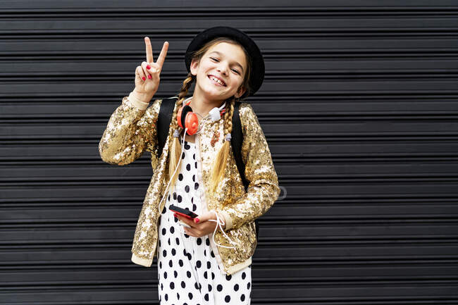 Portrait of happy girl with smartphone wearing hat and golden sequin jacket showing victory sign — Stock Photo