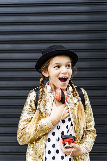 Portrait of astonished girl with headphones and smartphone wearing hat and golden sequin jacket — Stock Photo