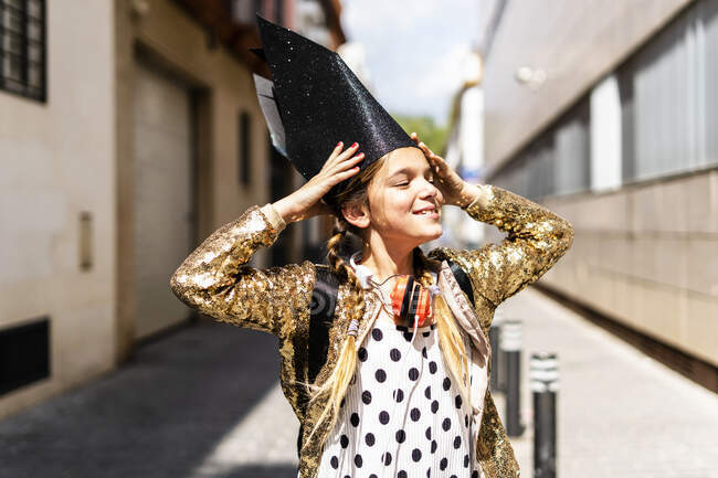 Portrait of smiling girl wearing black crown and golden sequin jacket — Stock Photo
