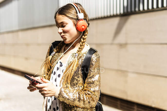 Smiling girl wearing golden sequin jacket and headphones looking at cell phone — Stock Photo