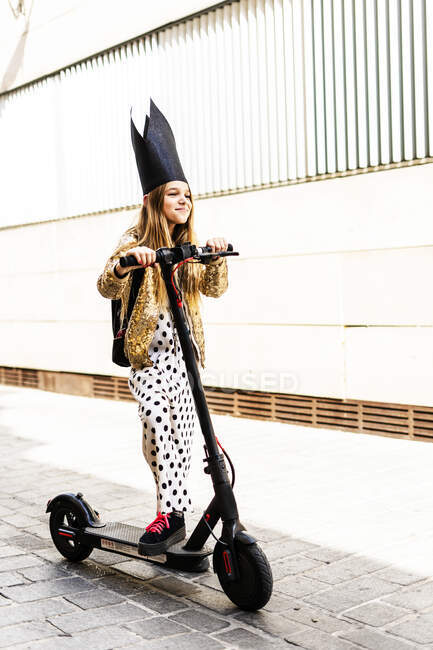 Portrait of smiling girl with E-scooter wearing black crown, golden sequin jacket and polka dot jumpsuit — Stock Photo