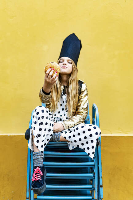 Girl wearing black crown sitting on stack of chairs holding hamburger — Stock Photo
