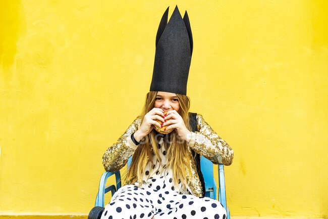 Portrait of girl wearing black crown eating Hamburger — Stock Photo