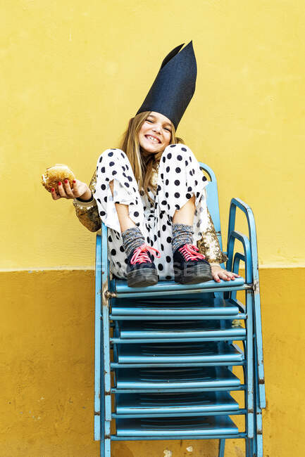 Portrait of laughing girl wearing black crown sitting on stack of chairs eating Hamburger — Stock Photo